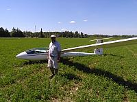 A Man With His Glider in an Alfalfa Field